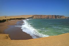Green Ocean, Red Beach, Yellow Cliff and Blue Sky at Paracas, Peru Royalty Free Stock Images