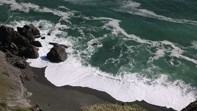 Green ocean, white waves and black beach stock video footage