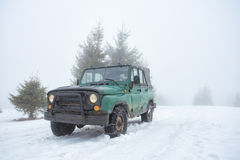 Green off-road vehicle on the snow-covered mountain Stock Photos