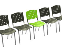 Green office chair among black ones Royalty Free Stock Images