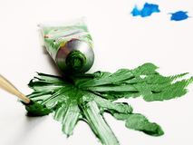 Green oil color fleck. Spilled green oil color spots and strokes with tube and brush Royalty Free Stock Photos