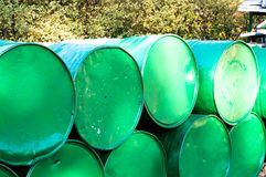 Green oil drums stacked sideways on top of each other. Green oil drums stacked on top of each other with plants in the background. Perfect image to show green Royalty Free Stock Photos