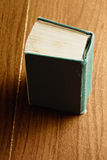 Green old book. Over wooden tabletop Stock Photography