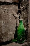 Green Old Bottle. Green glass ols bottle with dust and spider webs forgotten on a porch in a abandoned house in a remote and isolated village Royalty Free Stock Photography