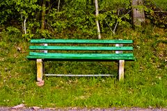 Green old lonely park bench in nature royalty free stock images