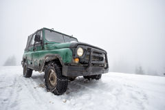 Green old off-road vehicle on the snow-covered mountain Royalty Free Stock Photo