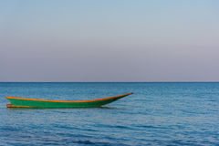 A green old wooden long tail boat floats in a calm still sea at Stock Photography