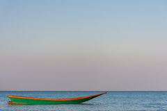 A green old wooden long tail boat floats in a calm still sea at Stock Images