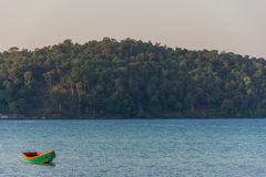 A green old wooden long tail boat floats in a calm still sea at Royalty Free Stock Image