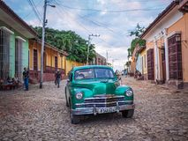 A green oldtimer taxi  in the Streets of Trinidad. A green oldtimer  plymouth serving as a taxi in the cobblestone streets of Trinidad Stock Images