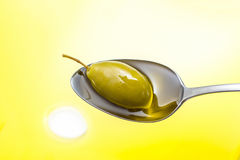 Green olive in full oil spoon on, top view Royalty Free Stock Image