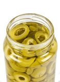 GREEN OLIVE SLICE. Slice of green olive in glassy jar isolated in white stock photography