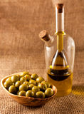Green olives. And olive oil on hessian Stock Photo