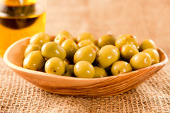 Green olives. In a wooden bowl on hessian Stock Image