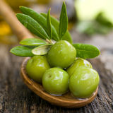Green olives. On a wooden spoon Stock Images