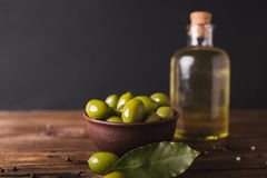 Green olives, bay leaf . Olive oil in a glass bottle.. Olives on a black background. Copyspace Royalty Free Stock Photos