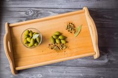 Green olives, bay leaf and spices on a wooden board stock images