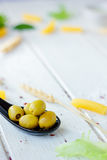 Green olives on black spoon over white wooden background. Stock Image