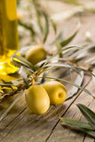 Green olives with bottle of oil. On a wooden table Royalty Free Stock Photography