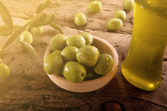 Green olives and bottle oil on an wooden table. Green olives on an wooden table after harvest Stock Photos