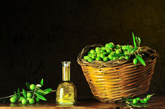 Green olives with bottle of olive oil. Basket of typical Sicilian olives freshly picked Stock Photos