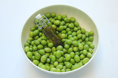 Green olives and a bottle of olive oil Stock Image