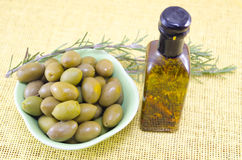Green olives and a bottle of virgin olive oil Stock Photography