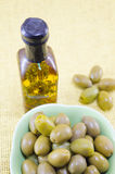 Green olives and a bottle of virgin olive oil Royalty Free Stock Photos