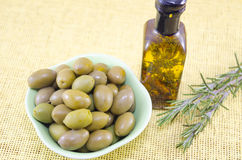 Green olives and a bottle of virgin olive oil Stock Photos