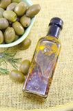 Green olives and a bottle of virgin olive oil Royalty Free Stock Photo