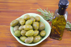 Green olives and a bottle of virgin olive oil. Fresh green olives and a bottle of virgin olive oil on a wooden table Stock Photo