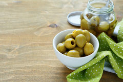 Green olives in bowl and jar Stock Photos