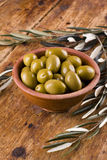 Green olives in a ceramic bowl arranged with leaves Royalty Free Stock Photo