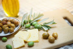 Green olives with cheese and olive branch on a wooden board. Backlight Royalty Free Stock Photography