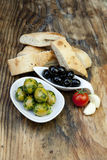 Green olives with fresh bread and herbs Stock Photos