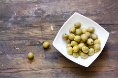 Green olives in marinade. Pickled green olives in white bowl, standing on a wooden table royalty free stock photos