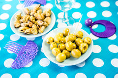 Green olives, mussels and costume jewelry Royalty Free Stock Photo