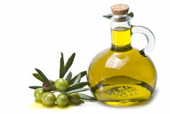 Green olives and oil. A jar with olive oil and some green olives isolated over a white background Stock Photo
