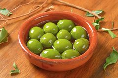 Green olives in oil Stock Photos