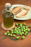 Green olives, oil and bread. Green olives with a bottle of fresh oil and bread slices in a dish over a wood table Stock Photo