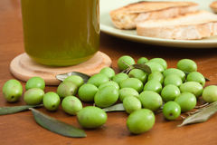 Green olives, oil and bread. Green olives with a bottle of fresh oil and bread in the background Royalty Free Stock Images