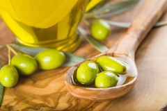 Green olives and oil on a wooden spoon Stock Photography