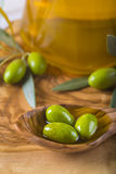 Green olives and oil on a wooden spoon Stock Photo