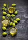 Green olives, olive branch and olive oil on a dark wooden board royalty free stock image