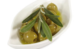 Green olives in olive oil. With branch on a plate Royalty Free Stock Photo