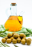 Green olives and olive oil. Green olives,  olive oil and olives leaves on a white background Royalty Free Stock Images