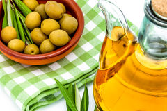 Green olives and olive oil. Green olives,  olive oil and olives leaves on a white background Stock Photography