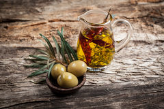 Green olives and olive oil with spice. On wooden table Stock Photo