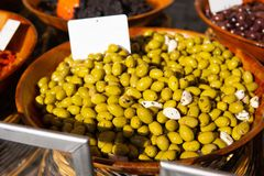 Green olives and pickled garlic at farmers market for sale stock photography
