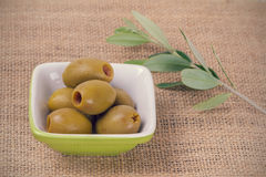 Green Olives. Pitted Green Olives in a Small Dish with an Olive Branch Stock Photos
